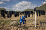 May 5, 2018: KANENGUERERE, ANGOLA - Clean HALO uniforms and body armor hang from the perimeter fence to dry at the end of the working week.  These deminers are working under extremely difficult circumstances in Kanenguerere.  Not only is extremely hot - with snakes and scorpions common - but much of the mined area is on the side of an extremely steep hill, making every step dangerous. The area was mined during the civil war by government forces to protect the nearby railway line that can be seen in the background, as well as various troop positions. It is currently used by roughly 170 people including village residents and nomadic herders - many of whom are young children - who pass through uncleared land every day.