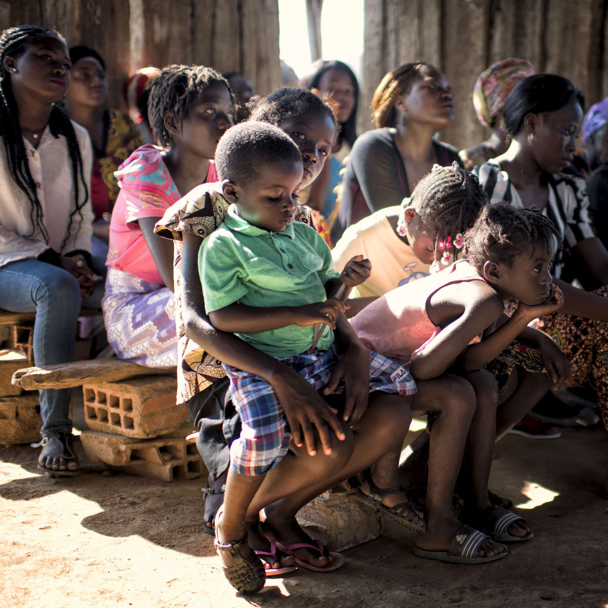 May 6, 2018: KANENGUERERE, ANGOLA - Four year-old Maxi sits on his older sister Regina's lap during church services in Kanenguerere village on Sunday morning. The HALO team has Sundays off, so the day is spent going to church, relaxing, and getting caught up on work.  The village is very small, so the HALO women make up the bulk of the worshippers and have set up a church committee to help out with the church affairs, while still offering a place of respect to the women of the village.  These deminers are working under extremely difficult circumstances in Kanenguerere.  Not only is extremely hot - with snakes and scorpions common - but much of the mined area is on the side of an extremely steep hill, making every step dangerous. The area was mined during the civil war by government forces to protect the nearby railway line that can be seen in the background, as well as various troop positions. It is currently used by roughly 170 people including village residents and nomadic herders - many of whom are young children - who pass through uncleared land every day.