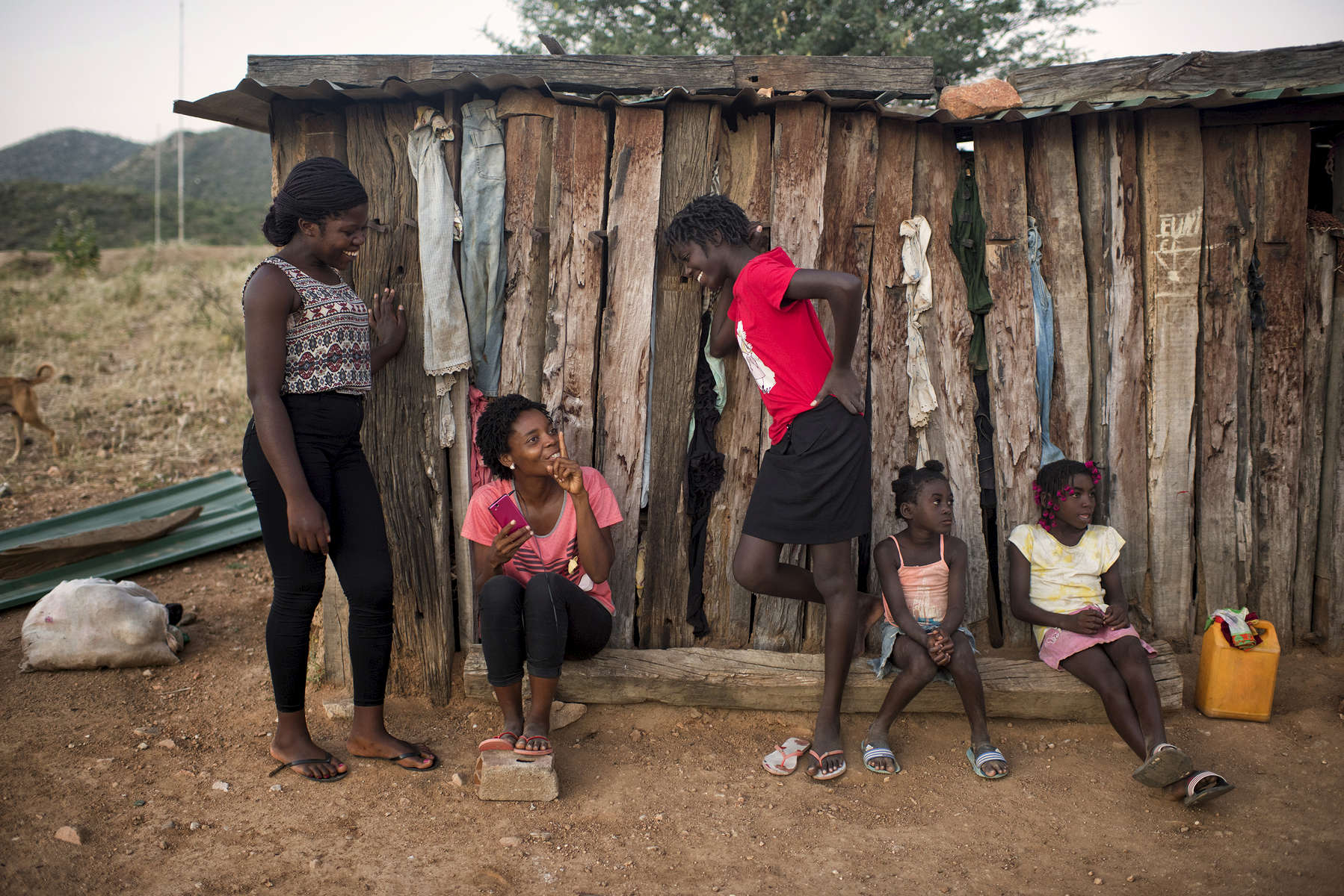 May 6, 2018: KANENGUERERE, ANGOLA - HALO deminers Imaculada Celestino and Suzana Soares visit with some of the children of Kaneguerere village - fourteen year-old Aurora, Suzy and Wandi on Sunday afternoon. The family moved into the village recently so that the children could go to school, and they have a small plot of land by the river where they grow a few vegetables.  The girls, especially, love the HALO deminers and want them to stay in the village forever. The HALO team has Sundays off, so the day is spent going to church, relaxing, and getting caught up on work.  These deminers are working under extremely difficult circumstances in Kanenguerere.  Not only is extremely hot - with snakes and scorpions common - but much of the mined area is on the side of an extremely steep hill, making every step dangerous. The area was mined during the civil war by government forces to protect the nearby railway line that can be seen in the background, as well as various troop positions. It is currently used by roughly 170 people including village residents and nomadic herders - many of whom are young children - who pass through uncleared land every day.