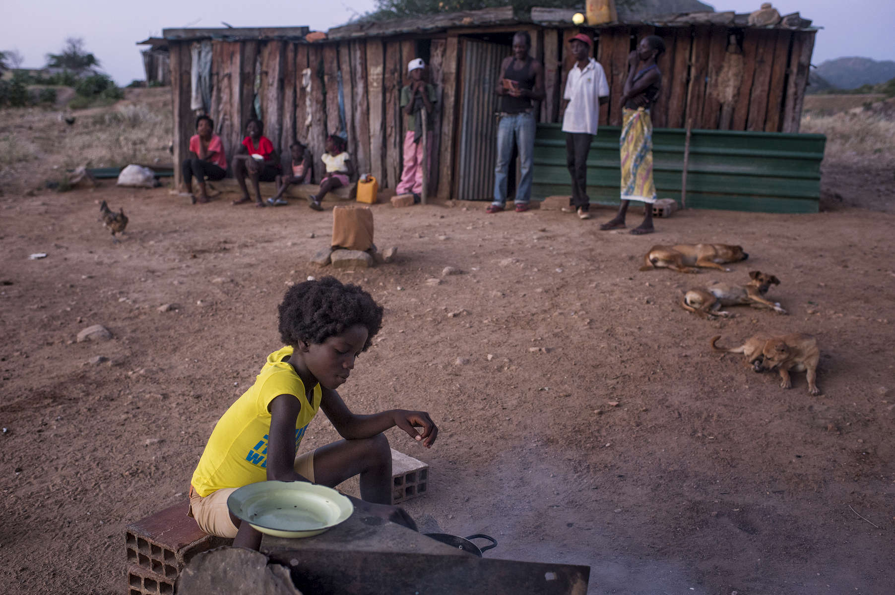 May 6, 2018: KANENGUERERE, ANGOLA - Eleven year-old Regina helps to prepare dinner for her family in front of their home in Kanenguerere Village. The family moved into Kanenguerere village recently so that the children could go to school, and they have a small plot of land by the river where they grow a few vegetables.  The girls, especially, love the HALO deminers and want them to stay in the village forever. The HALO team has Sundays off, so the day is spent going to church, relaxing, and getting caught up on work.  These deminers are working under extremely difficult circumstances in Kanenguerere.  Not only is extremely hot - with snakes and scorpions common - but much of the mined area is on the side of an extremely steep hill, making every step dangerous. The area was mined during the civil war by government forces to protect the nearby railway line that can be seen in the background, as well as various troop positions. It is currently used by roughly 170 people including village residents and nomadic herders - many of whom are young children - who pass through uncleared land every day.