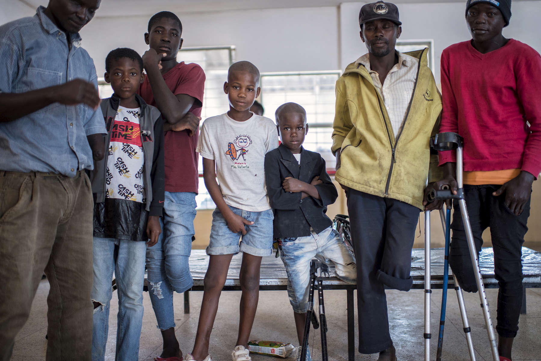 May 10, 2018: HUAMBO, ANGOLA - A group of boys who were seriously wounded while playing with a mortar round in December 2016 sit with older men, who are also mine accident victims at the rehabilitation center of a hospital in Huambo. Twelve year-old Antonio (patterned shirt), fourteen year-old Jeremy (red shirt), ten year-old Mario (white shirt) and eight year-old Manuel (black jacket) survived the accident, while their friend Frederico, ten, was killed. While there is an enormous need for prosthetic limbs in Angola, a country with an enormous number of mines laid during the civil war, they are unable to afford to import the materials necessary to make them.