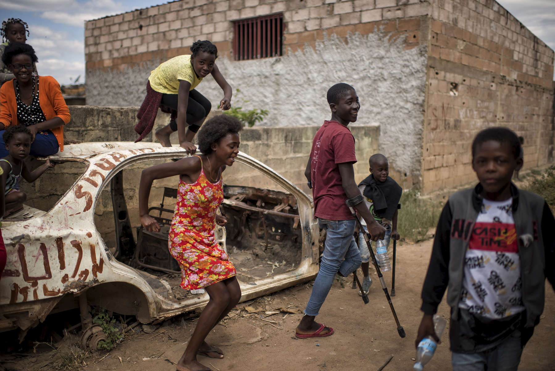 May 10, 2018: HUAMBO, ANGOLA -Fourteen year-old Jeremy clowns around with some friends outside the yard his family's home in Huambo. He is the youngest of a group of boys who were seriously wounded while playing with a mortar round in December 2016 sit with older men, who are also mine accident victims at the rehabilitation center of a hospital in Huambo. Twelve year-old Antonio (patterned shirt), fourteen year-old Jeremy (red shirt), ten year-old Mario (white shirt) and eight year-old Manuel (black jacket) survived the accident, while their friend Frederico, ten, was killed. While there is an enormous need for prosthetic limbs in Angola, a country with an enormous number of mines laid during the civil war, they are unable to afford to import the materials necessary to make them.