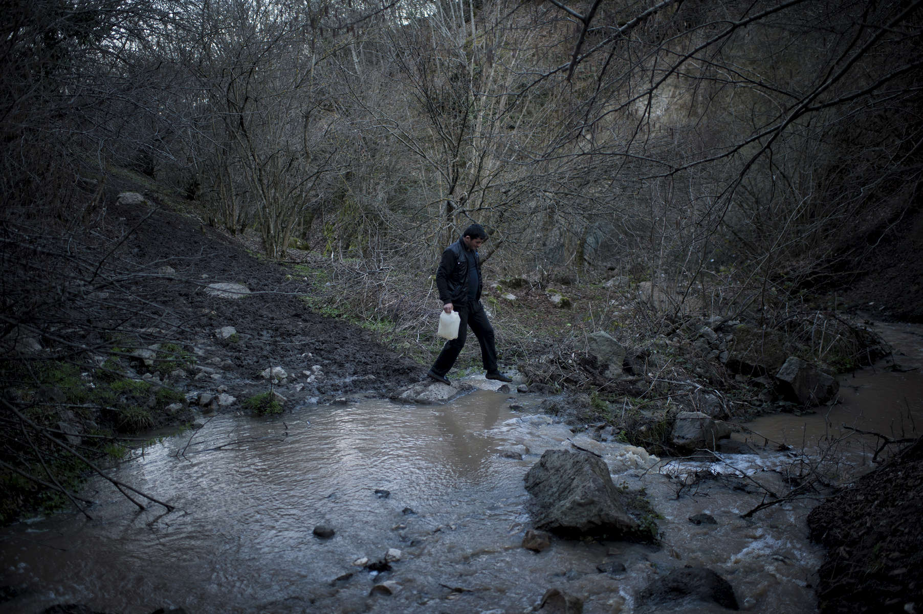 A young man walks to get water from a spring near Nor Kilikia village.   HALO has cleared land that allows for water pipes to be run into the village, but before that, all water needed to be collected from this river.