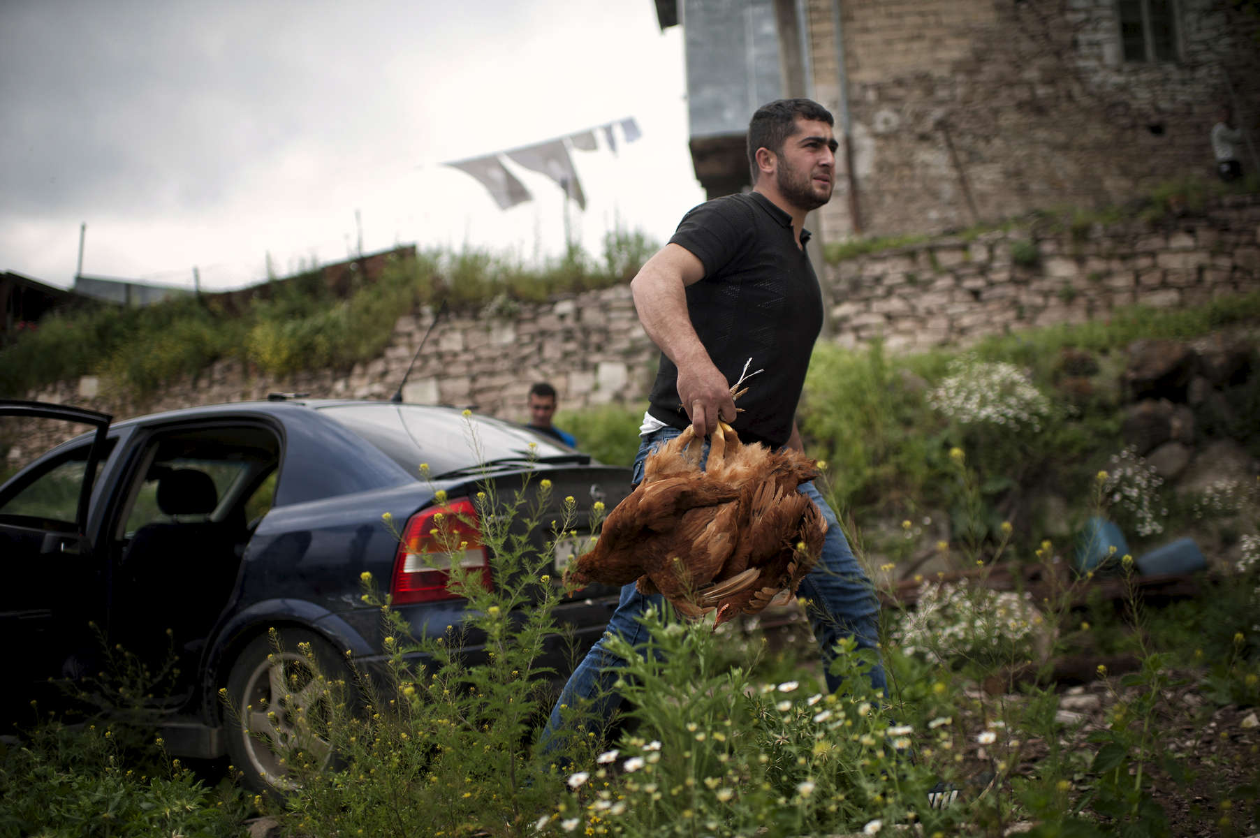 The son of a beneficiary (NAME TK) unloads a carload of chickens in Harav village. NAMES TK