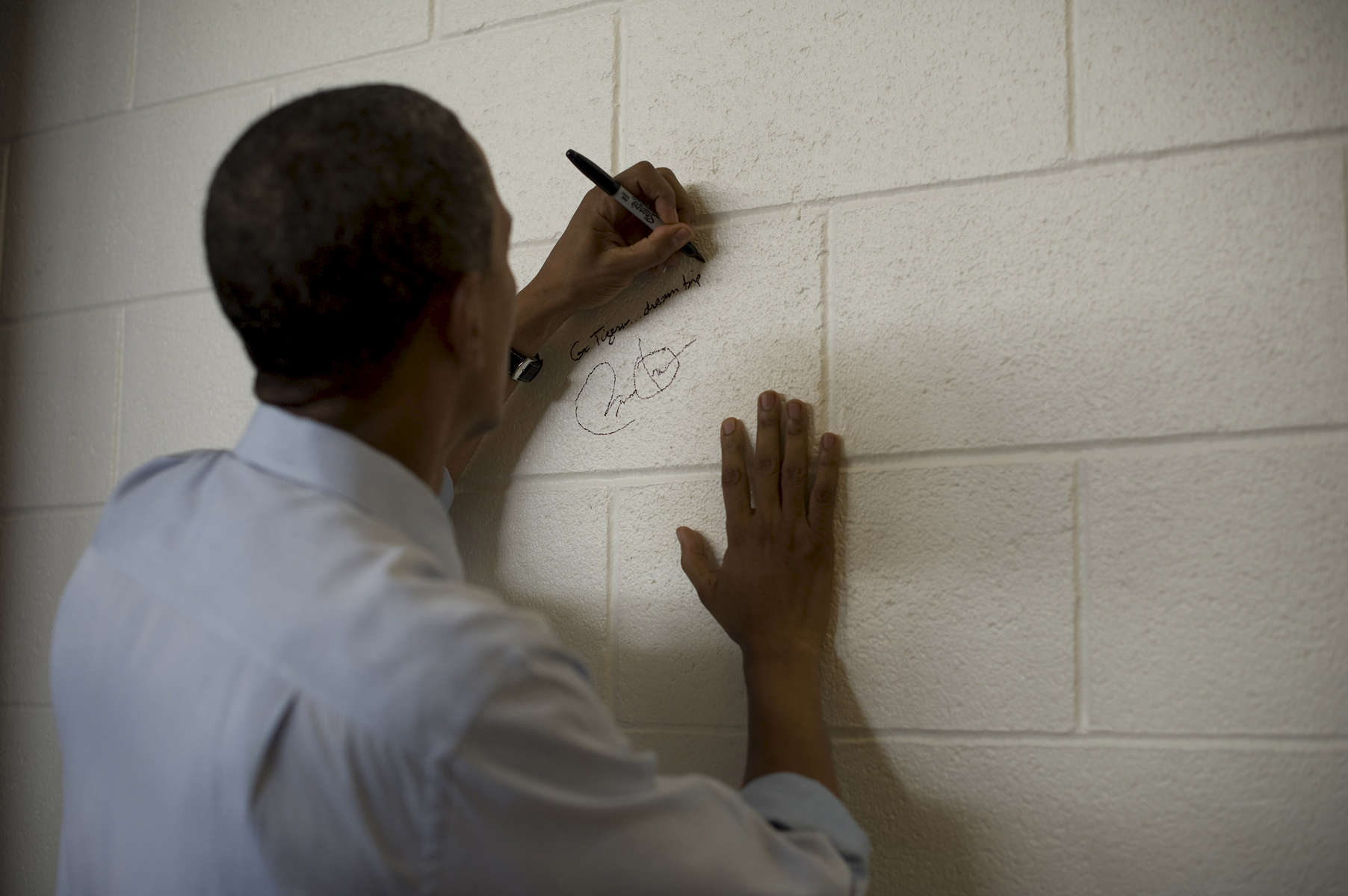 August 8, 2012- GRAND JUNCTION, CO: President Barack Obama signs the wall of Grand Junction High School, as is the school's tradition for distinguished guests, after a rally in Grand Junction, CO on August 8th, 2012. (Scout Tufankjian for Obama for America/Polaris)