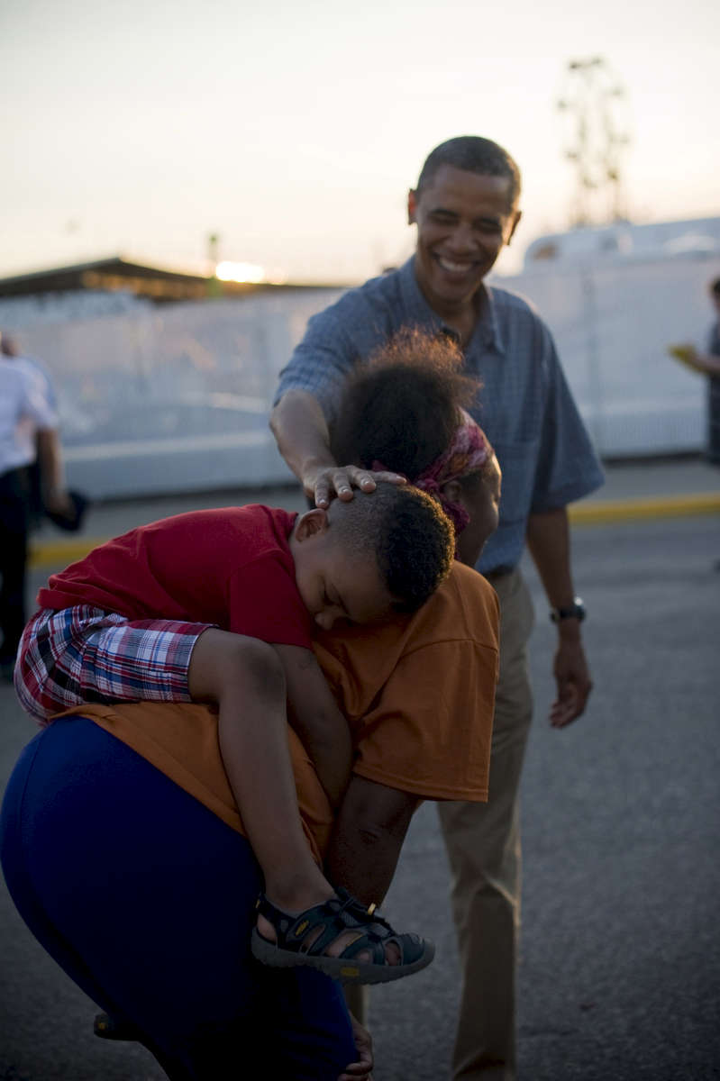 August 13, 2012- Des Moines, IA: President Barack Obama rubs the head of a little boy asleep on his mother's back at the Iowa State Fair in Des Moines, IA. (Scout Tufankjian for Obama for America/Polaris)
