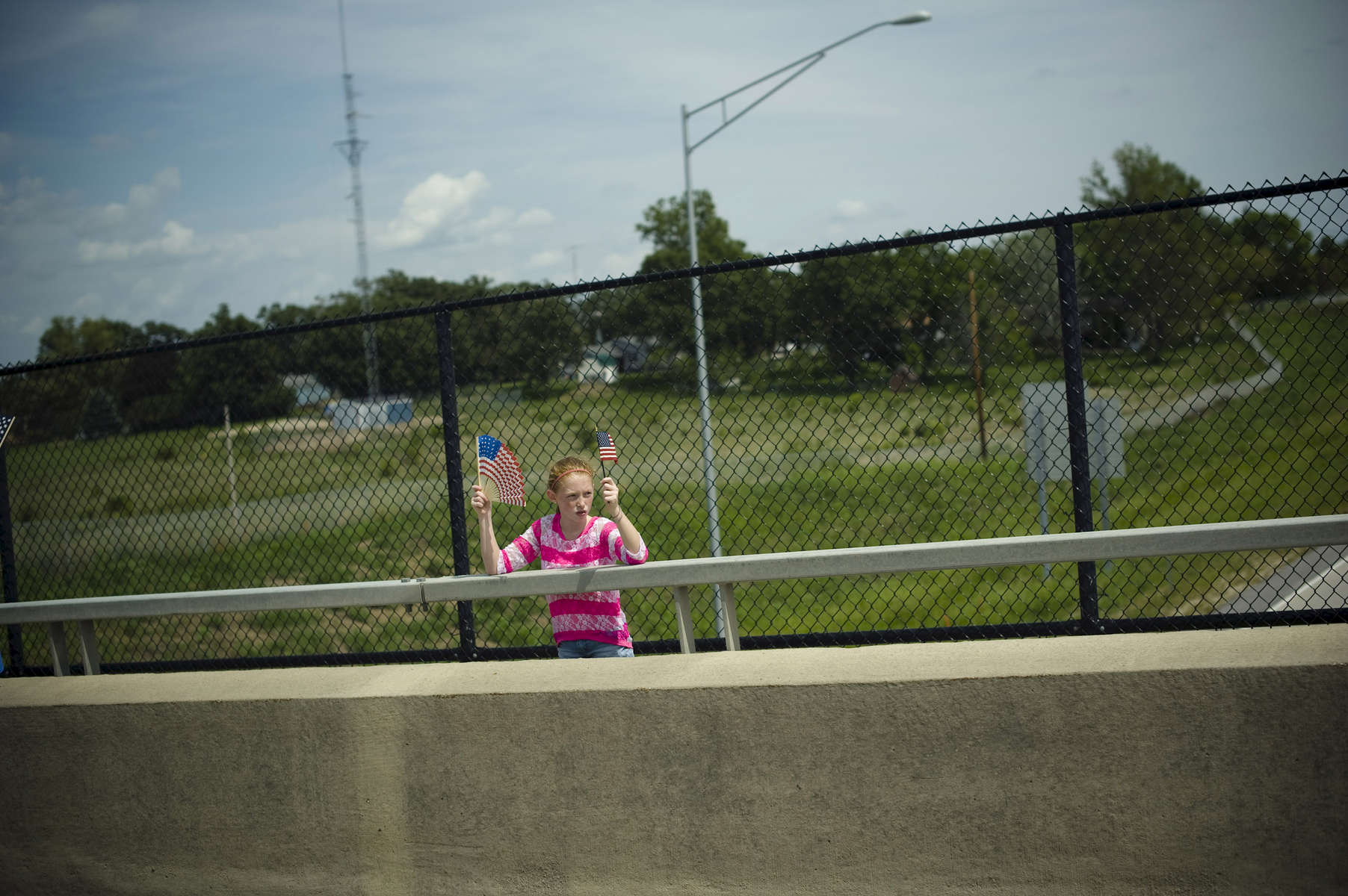 August 14, 2013 - HAVERHILL, IA: A young girl waves American flags as President Barack Obama's motorcade drives by her in Iowa. (Scout Tufankjian for Obama for America/Polaris)
