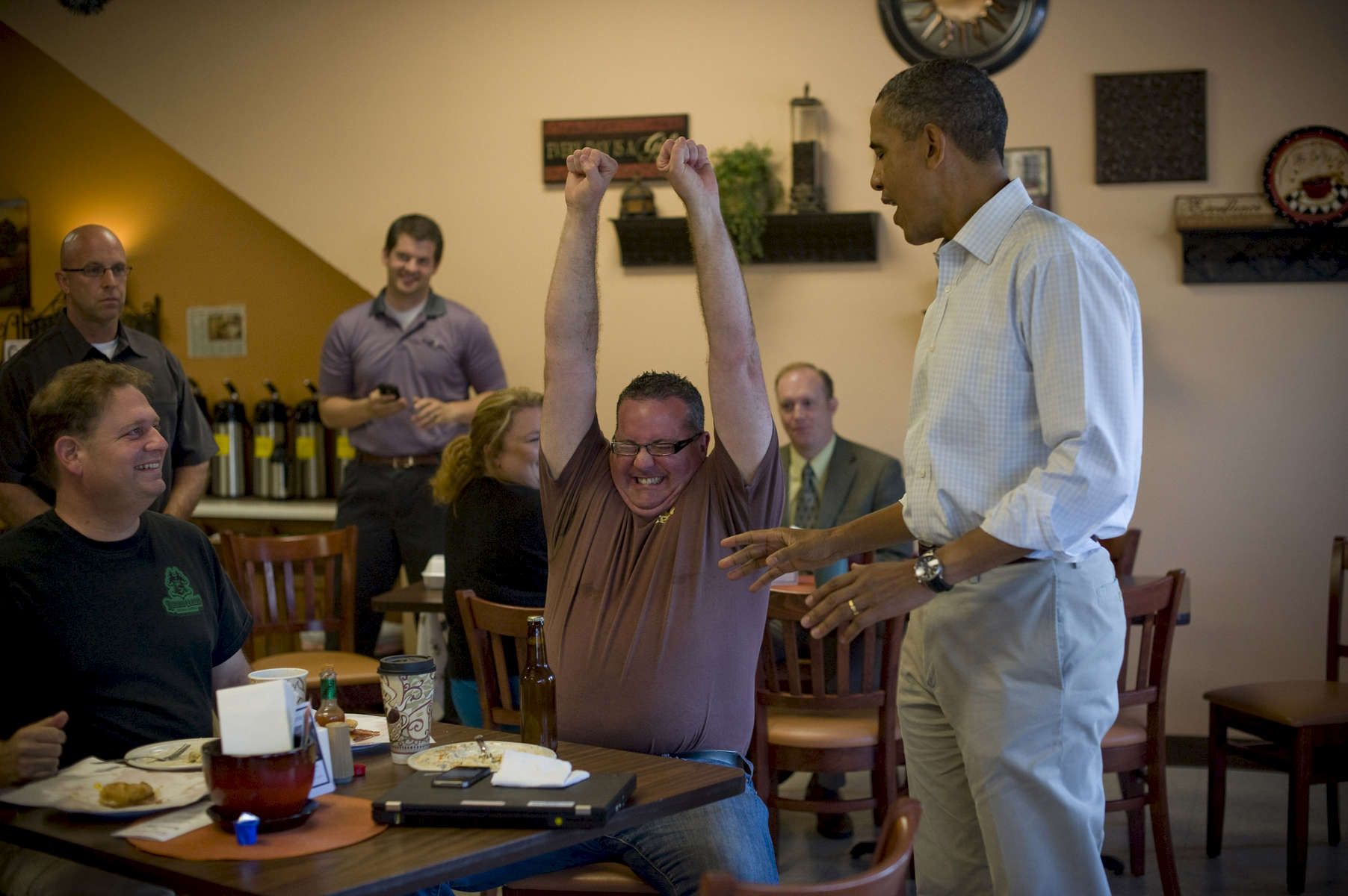 August 14, 2012- KNOXVILLE, IA: Brad Magerkurth, a traveling beer salesman from Minnesota, reacts as President Barack Obama presents him with a bottle of the White house home brewed beer in Knoxville, Iowa.  Magerkurth had stopped by the Coffee Connection in Knoxville while on a business trip and was shocked to find himself discussing beer with the President.  (Scout Tufankjian for Obama for America/Polaris)