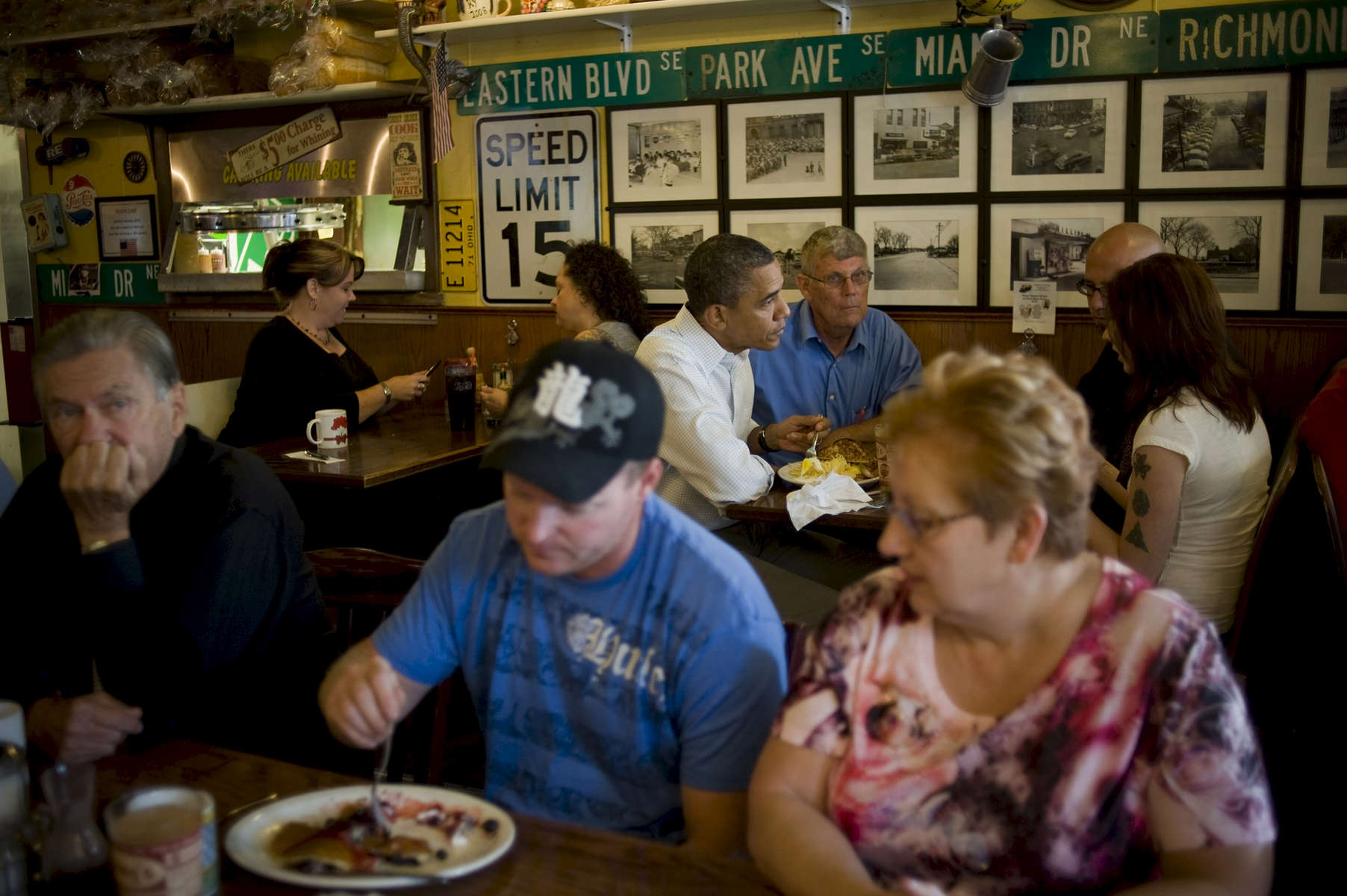 August 15, 2012- CEDAR RAPIDS, IA: Patrons of Riley's Cafe in Cedar Rapids eat as President Barack Obama shares breakfast with three US Military Veterans. (Scout Tufankjian for Obama for America/Polaris)