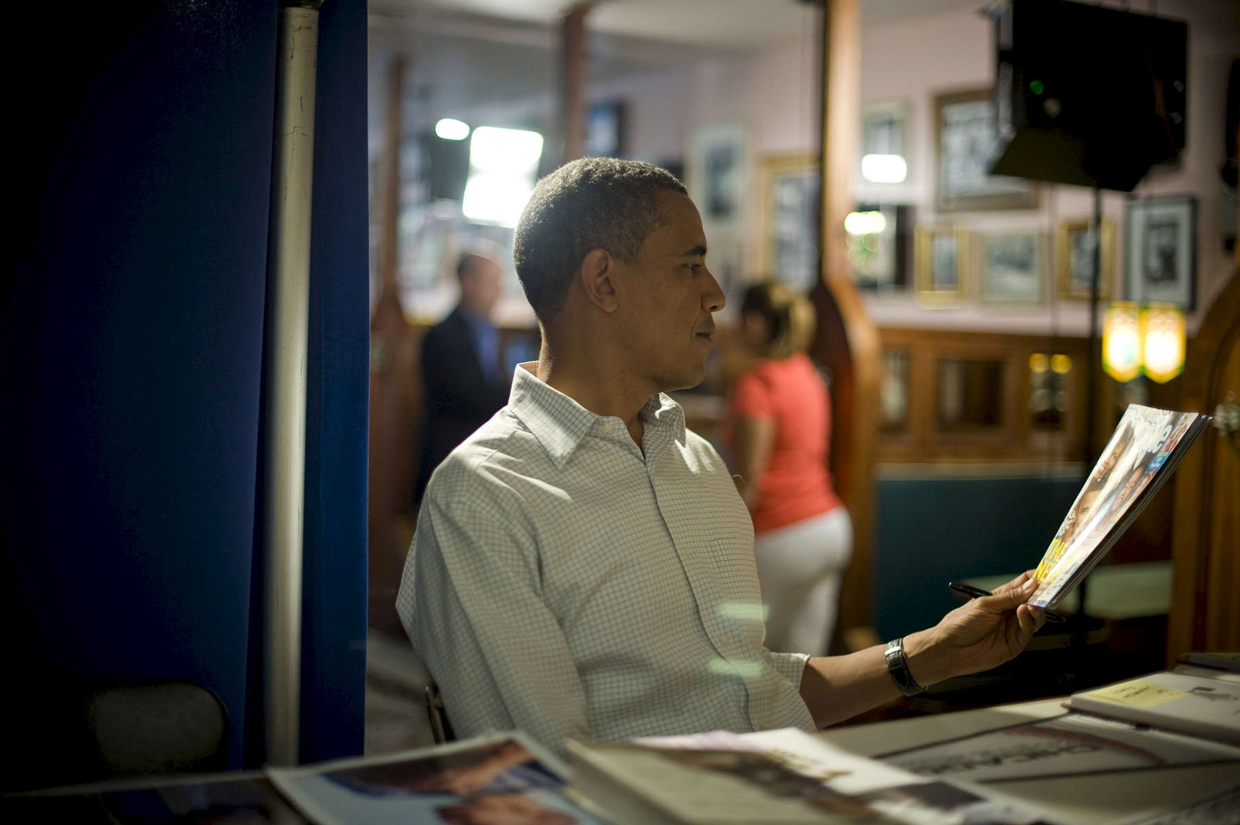 August 15, 2012- DAVENPORT, IA: President Barack Obama looks nostalgic as he signs a copy of a magazine with pictures of his daughters when they were much younger on the cover backstage at Logomarcino's Ice Cream Shoppe in Davenport, Iowa. (Scout Tufankjian for Obama for America/Polaris)
