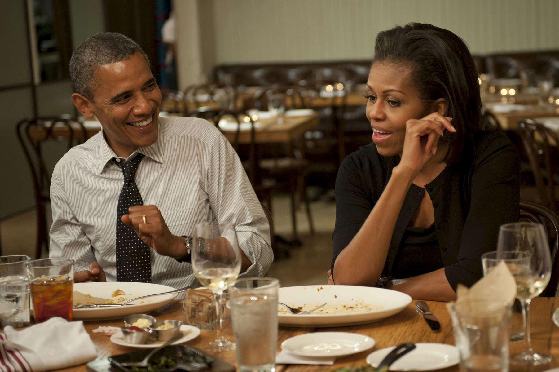 August 20, 2012 - WASHINGTON DC-  President Barack Obama and First Lady Michelle Obama show their dinner guests how they threaten to dance in public to embarrass their two daughters while dining at Mintwood Place in Washington DC. (Scout Tufankjian for Obama for America/Polaris)