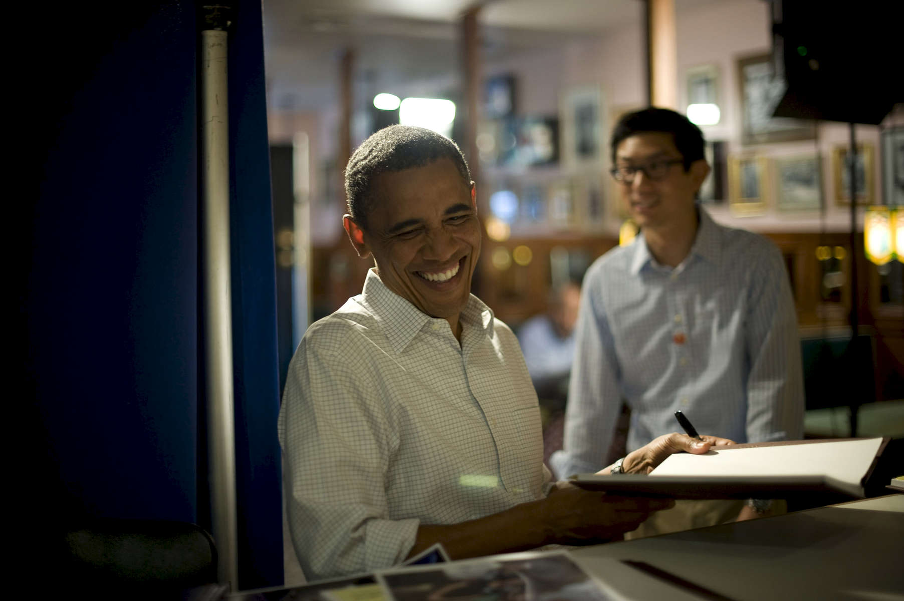 August 15, 2012- DAVENPORT, IA: President Barack Obama laughs as he signs a book backstage at Logomarcino's Ice Cream Shoppe in Davenport, Iowa. (Scout Tufankjian for Obama for America/Polaris)