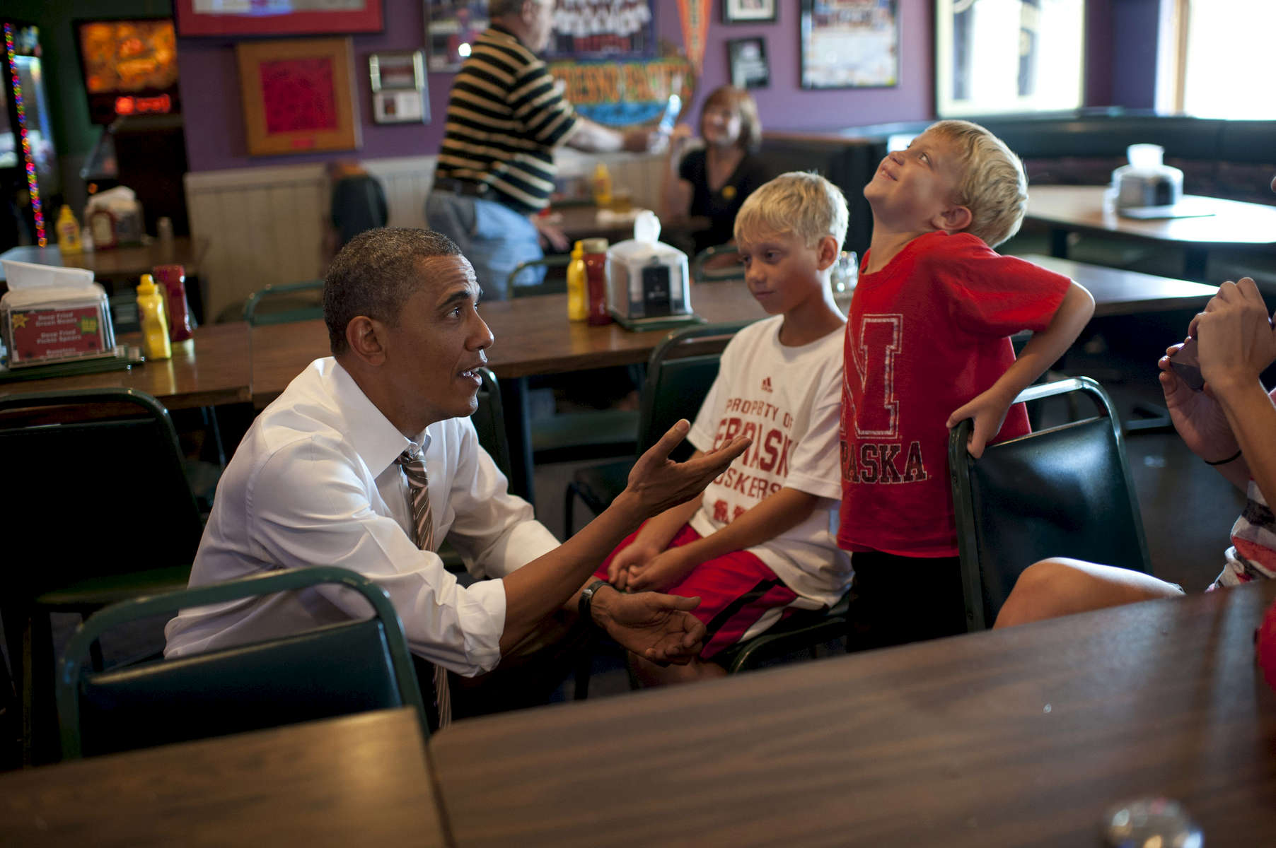 September 1, 2012 - Sioux City, IA: President Barack Obama teases two boys at Bob Roe's Point After sports bar in Sioux City, IA.  (Scout Tufankjian for Obama for America/Polaris)