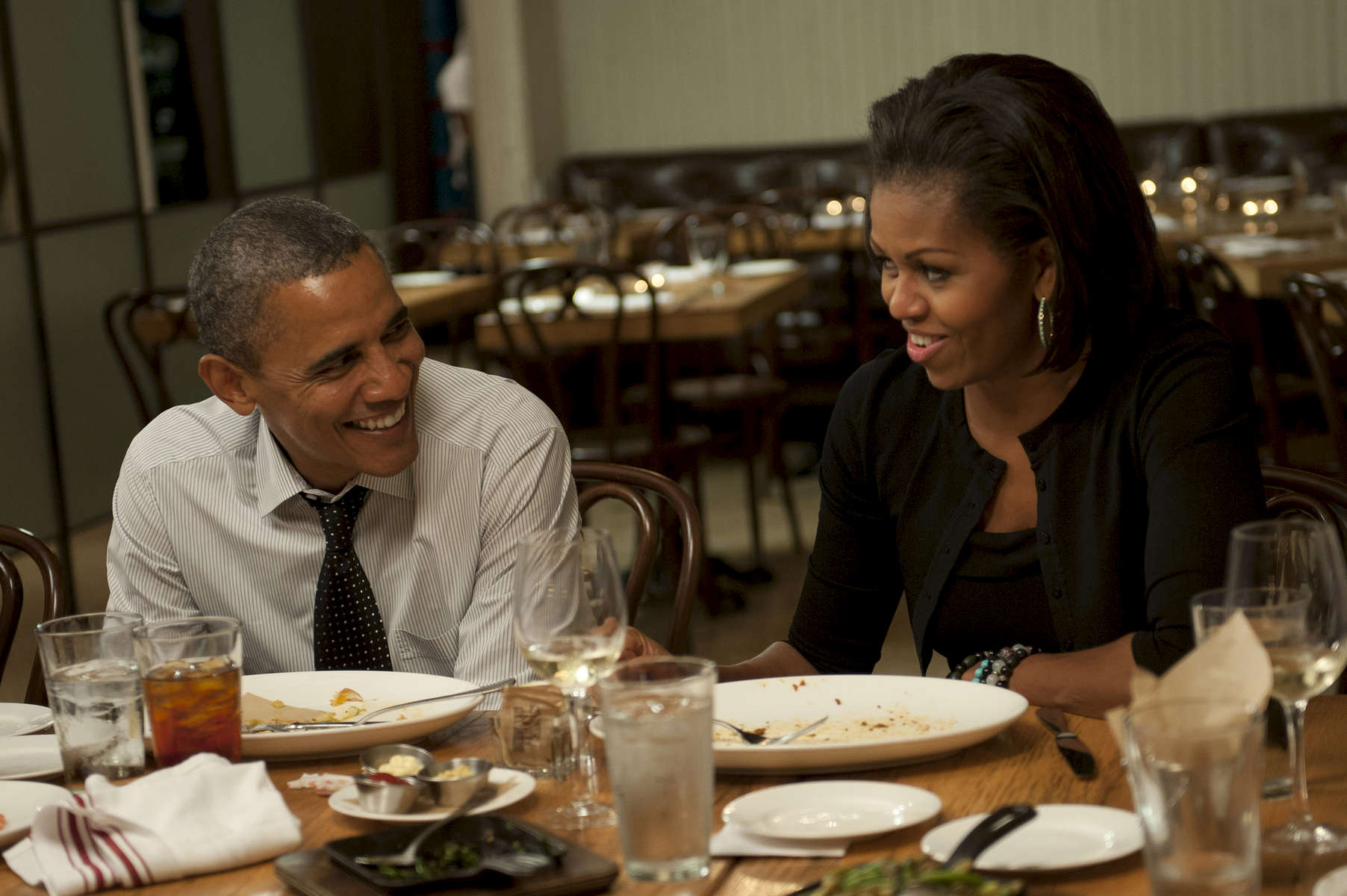 August 20, 2012 - WASHINGTON DC-  President Barack Obama and First Lady Michelle Obama grin at each other while dining at Mintwood Place in Washington DC. (Scout Tufankjian for Obama for America/Polaris)
