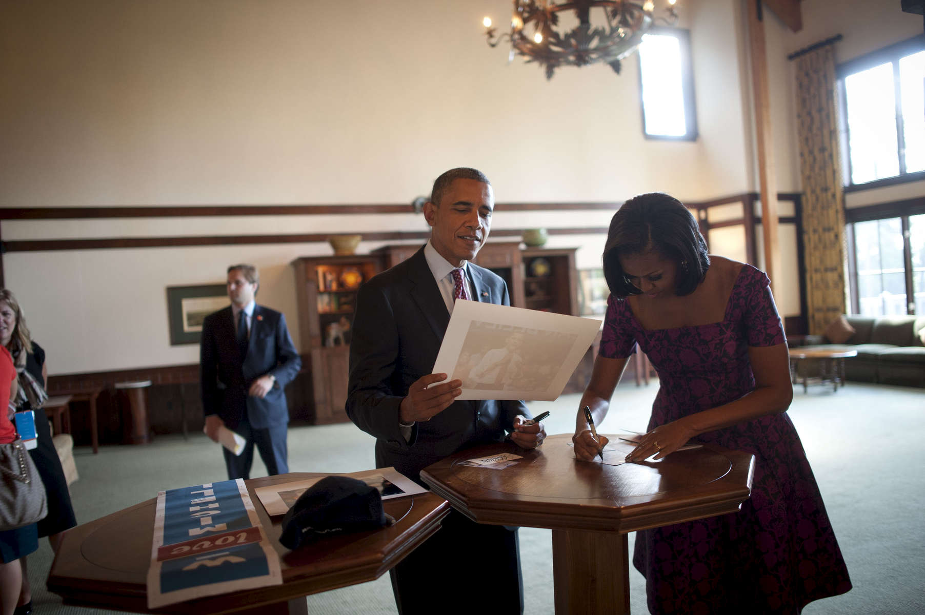 September 5, 2012 - CHARLOTTE, NC: President Barack Obama looks nostalgically at an old picture of himself speaking while he and his wife, First Lady Michelle Obama sign things for supporters during the Democratic National Convention. (Scout Tufankjian for Obama for America/Polaris)