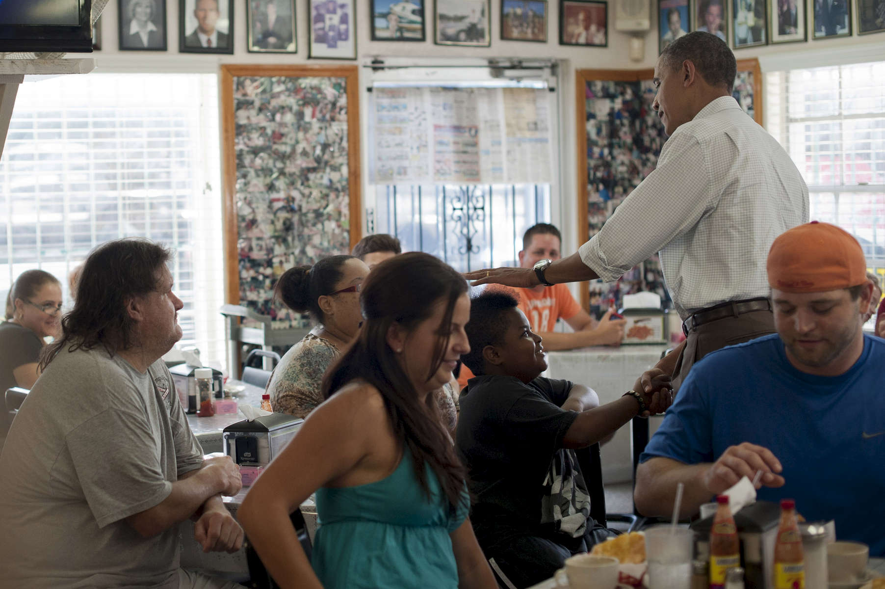 September 8, 2012 - Tampa, FL: President Barack Obama teases a young spikey-haired patron of the West Tampa Sandwich Shop and Restaurant in Tampa, FL. (Scout Tufankjian for Obama for America/Polaris)