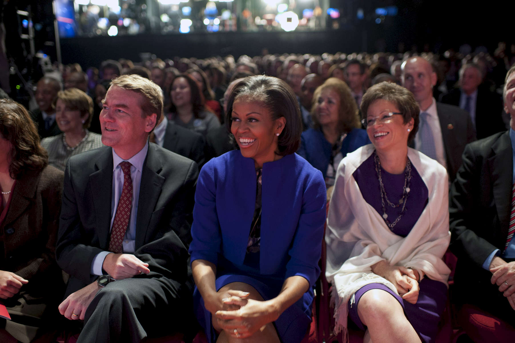 October 3, 2012 - Denver, CO:  First Lady Michelle Obama sits with Senator Michael Bennett and advisor Valerie Jarrett at the start of the first debate between President Barack Obama and former Governor Mitt Romney. (Scout Tufankjian for Obama for America/Polaris)