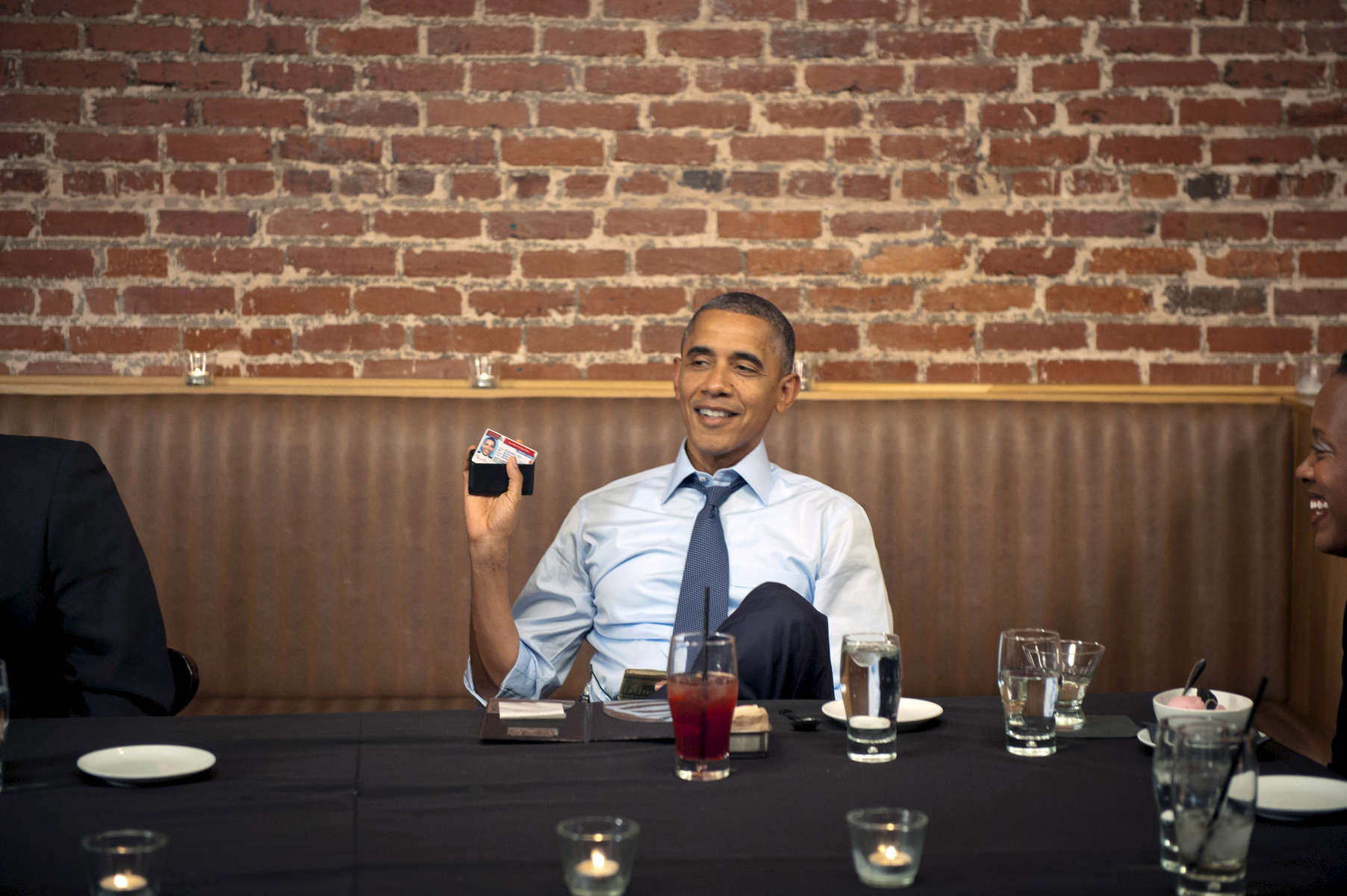 October 12, 2012 - Washington DC: President Barack Obama shows off his driver's license during a dinner at Smith Commons in Washington DC. (Scout Tufankjian for Obama for America/Polaris)