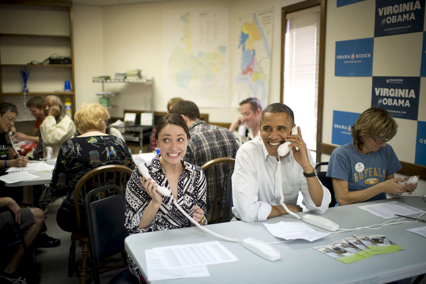 October 14, 2012 - Williamsburg, VA - A young woman reacts as President Barack Obama sits next to her to make phone calls at a campaign field office in Williamsburg, VA.  (Scout Tufankjian for Obama for America/Polaris)
