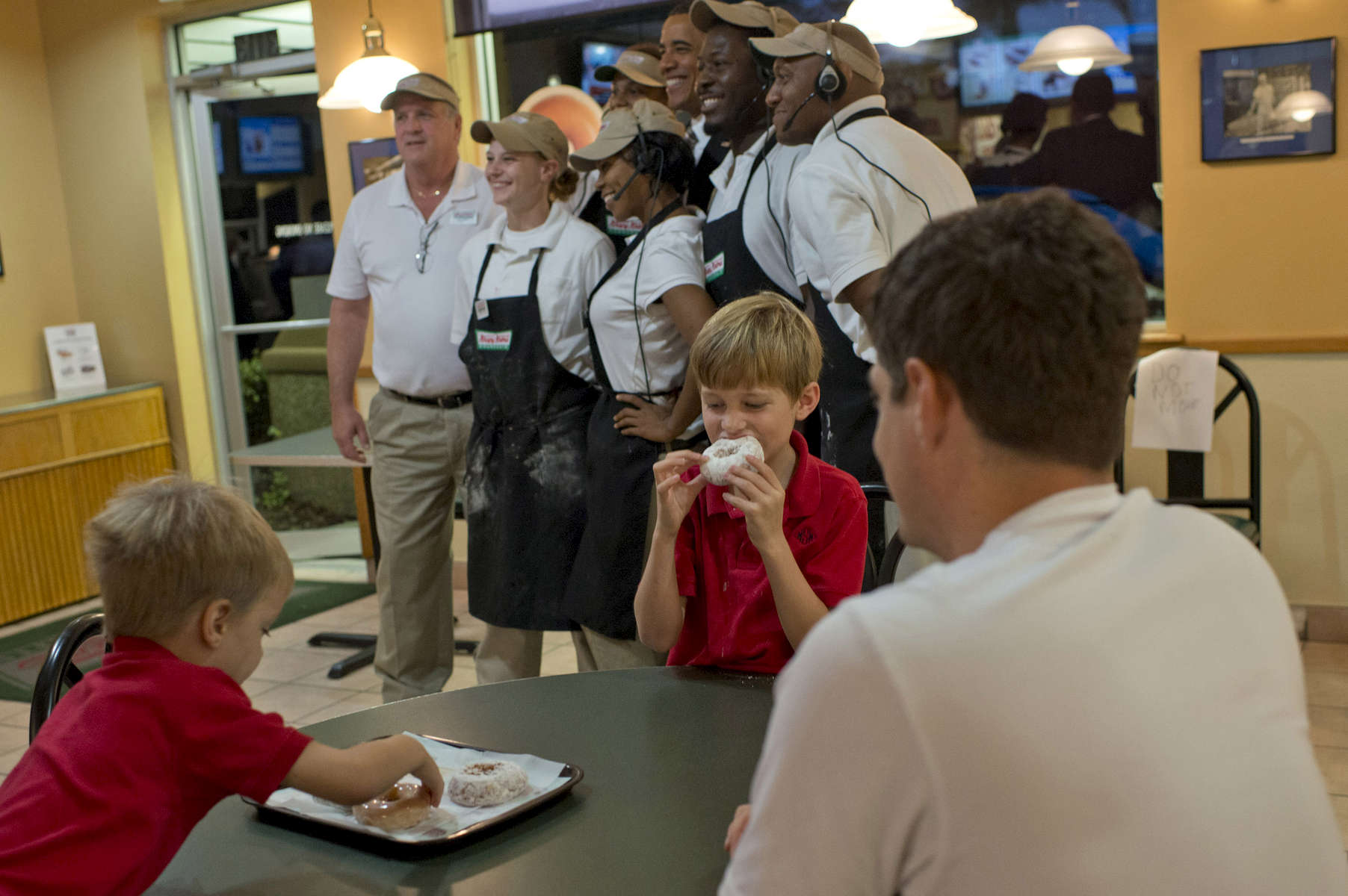October 25, 2012 - Tampa, FL:  Two boys continue to eat their Krispy Kreme donuts as President Barack Obama poses with workers at the doughnut shop during a 48 hour straight swing of campaign events. (Scout Tufankjian for Obama for America/Polaris)