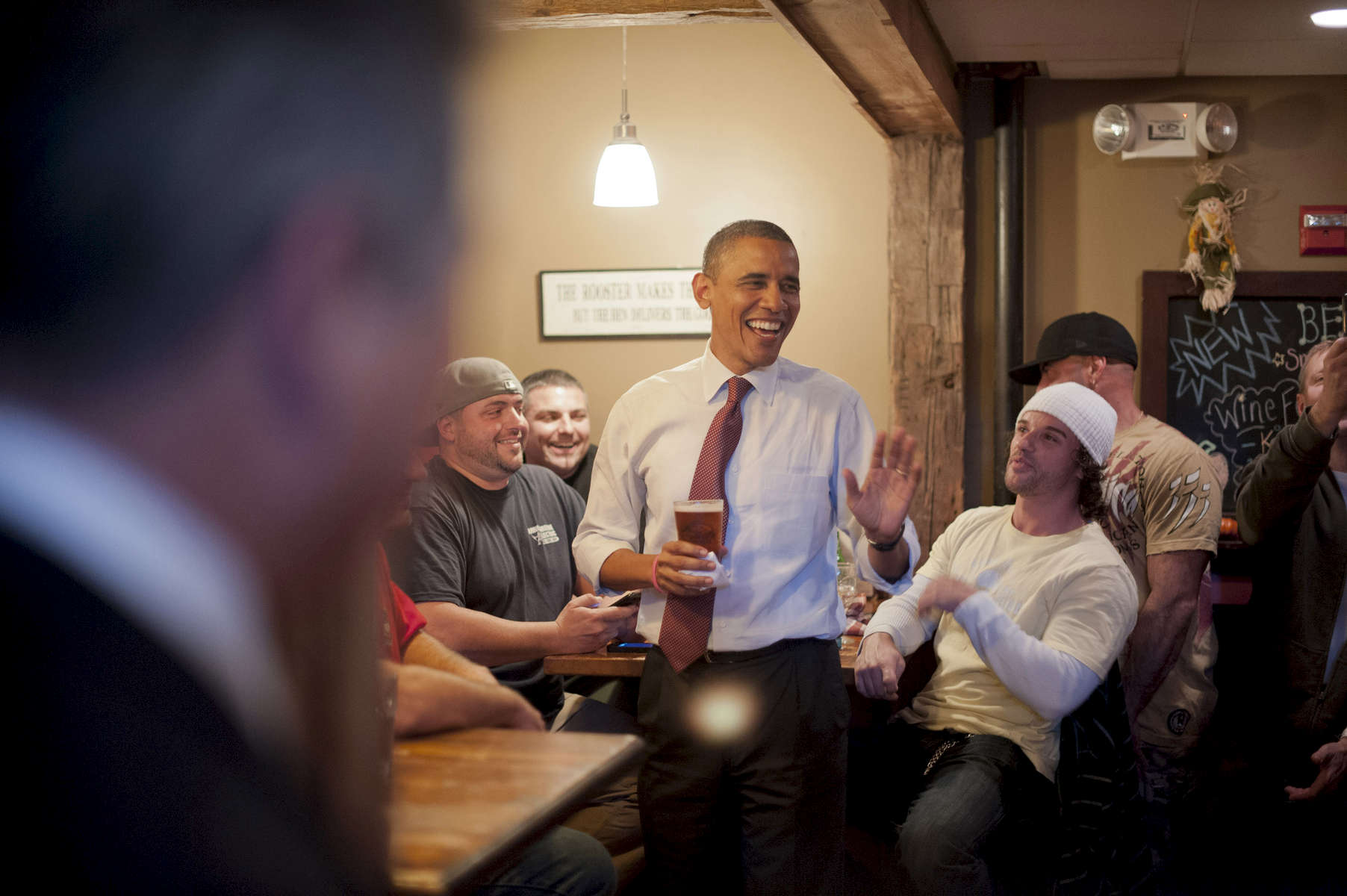 October 27, 2012 - Merrimack, NH:  President Barack Obama jokes around with patrons at the Common Man Pub in Merrimack, NH.  (Scout Tufankjian for Obama for America/Polaris)