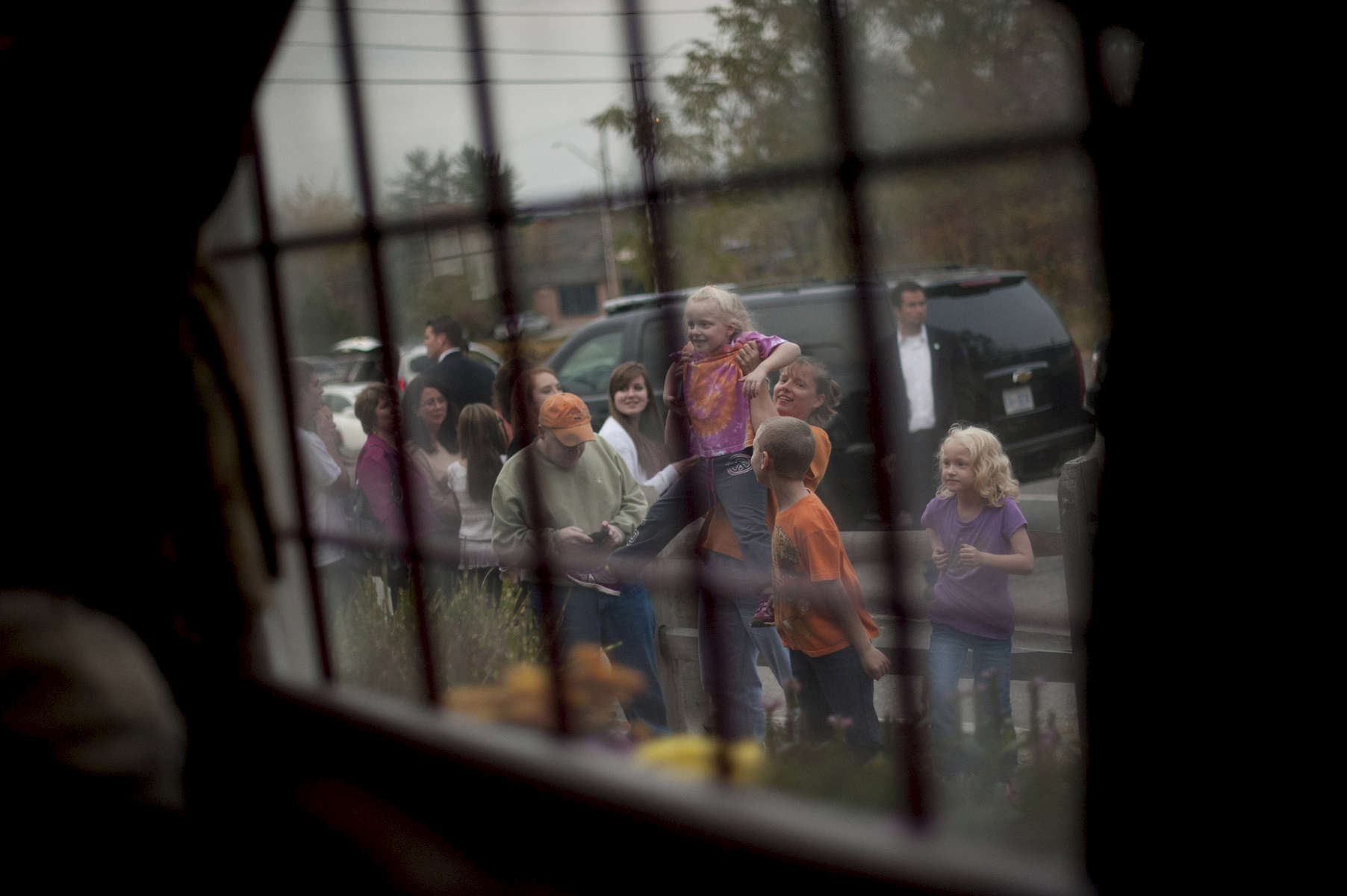 October 27, 2012 - Merrimack, NH:  A mother holds up her daughter so that she can see President Barack Obama through the window of the Common Man Pub in Merrimack, NH.  (Scout Tufankjian for Obama for America/Polaris)