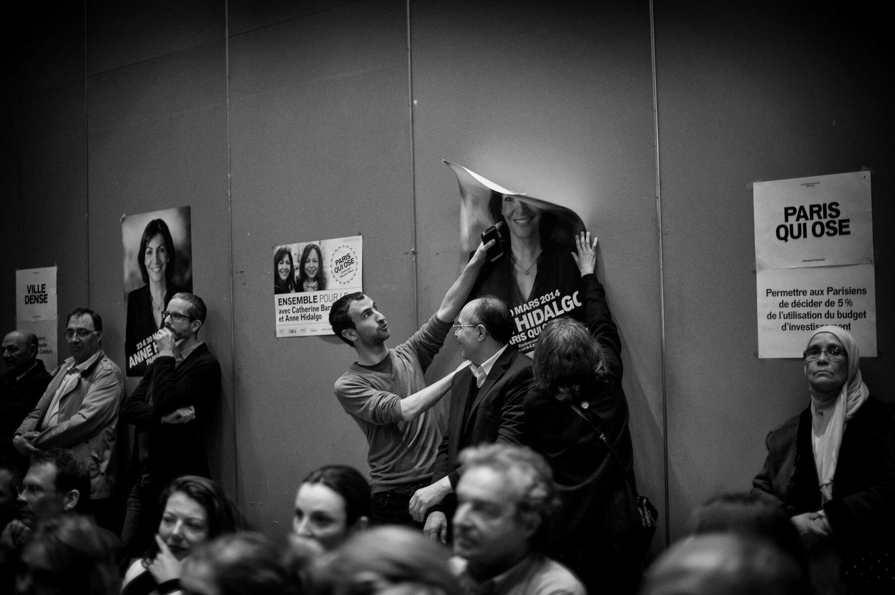 March 11, 2014.  PARIS, FRANCE- Supporters of mayoral candidate Anne Hidalgo try to keep a poster from falling as she speaks at a campaign event at Espace Reuilly in Paris' 12th Quarter.  For the first time in France's history, Paris will have a woman as a mayor - either Socialist Anne Hidalgo or Center-Right Nathalie Kosciusko-Morizet.  Photo by Scout Tufankjian