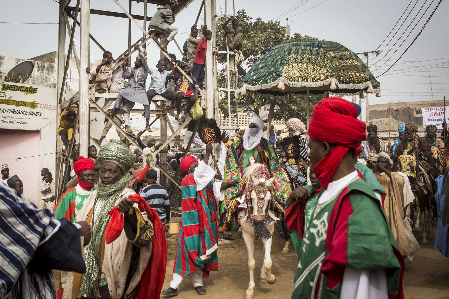 The Emir of Kano, Muhammed Sanusi II, surrounded by his guards and aides, rides his horse to the Fatahul Mubin Islamic School graduation through the Old City in Kano, NigeriaThe Emir of Kano is the fourth most powerful religious leader in Nigeria ruling the Kingdom of Kano which has been in existence for over 1000 years. The former Governor of the Central Bank of Nigeria, Muhammed Sanusi II, 56, was crowned in 2014, taking over the traditional role as a religious leader but also as an advisor to politicians, government employees, village chiefs and even settles disputes between individuals.Seen as a modern leader, Sanusi II has been a champion for girls education, women rights, job creation, development as well as the re-industrializing Kano State. But, as his methods of communication became just as advanced by using Facebook and Twitter via his aides, coupled with his radical thoughts on modern islam, many felt that he was being influenced by the west and a backlash began. Since then, the Emir has reduced/eliminated his involvement in social media as well as softened his approach with the conservative scholars.