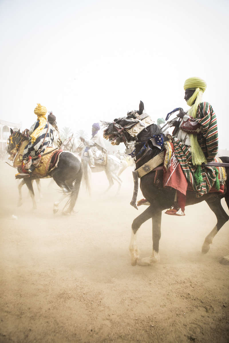 Members of the Emir of Kano, Muhammed Sanusi II's, court race their horses outside the palace in Kano, Nigeria