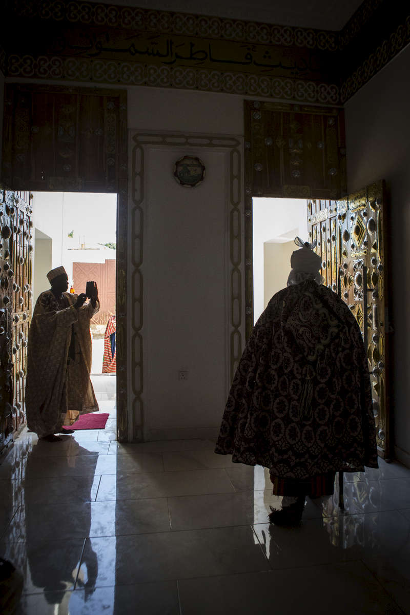 A man takes a photo of the Emir of Kano, Muhammed Sanusi II, as he leaves the inner palace in Kano, Nigeria