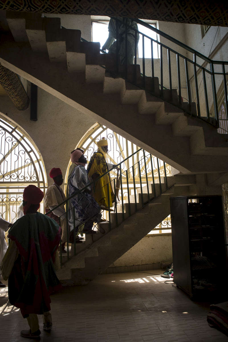 Mustafa Abba (yellow), the Emir of Kano's younger brother and personal secretary walks with his aides to his office in the palace in Kano, Nigeria