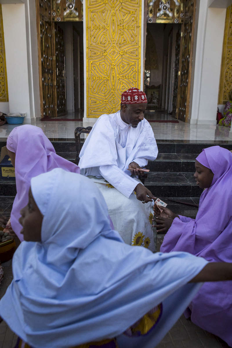 Kano, Nigeria- The Emir of Kano, Muhammed Sanusi II, gives alms (a 10 Naira note and candy) to girls after Friday prayers in Kano, Nigeria on Friday, January 19, 2018.The Emir of Kano is the fourth most powerful religious leader in Nigeria ruling the Kingdom of Kano which has been in existence for over 1000 years. The former Governor of the Central Bank of Nigeria, Muhammed Sanusi II, 56, was crowned in 2014, taking over the traditional role as a religious leader but also as an advisor to politicians, government employees, village chiefs and even settles disputes between individuals.Seen as a modern leader, Sanusi II has been a champion for girls education, women rights, job creation, development as well as the re-industrializing Kano State. But, as his methods of communication became just as advanced by using Facebook and Twitter via his aides, coupled with his radical thoughts on modern islam, many felt that he was being influenced by the west and a backlash began. Since then, the Emir has reduced/eliminated his involvement in social media as well as softened his approach with the conservative scholars. (Photo by Jane Hahn for the Washington Post)