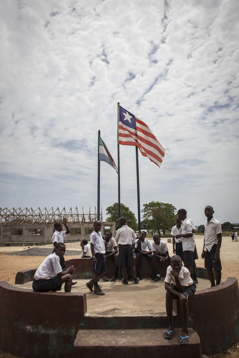 Students stand under the Liberian flag during a break at the R.S. Caufield Public School in Unification, Liberia