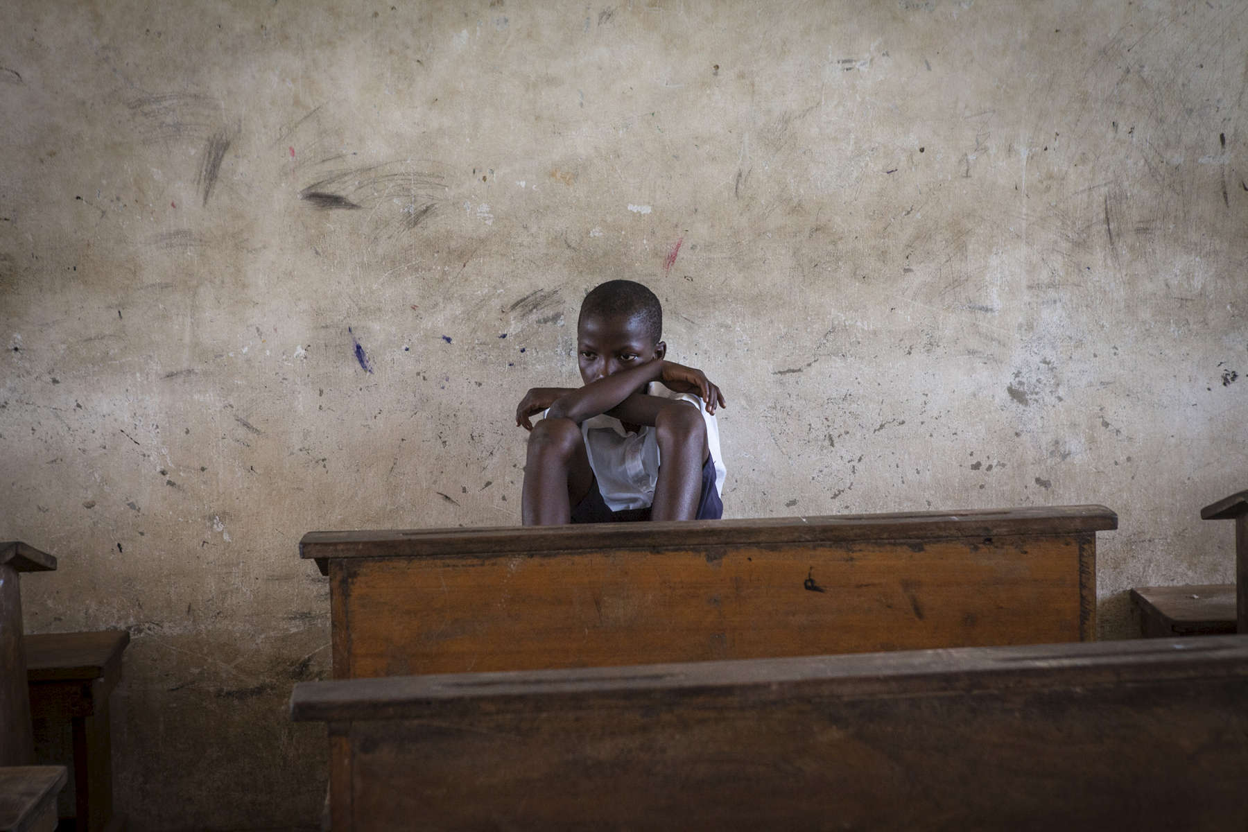 A student sits at the back of an empty classroom during recess at the R.S. Caufield Public School in Unification, Liberia