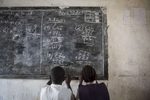 Students in Grade 2 work out math problems on the chalk board at the Kenlay Public School in Kenlay, Liberia