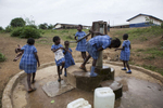 Students pump water during a break outside of the Upper Careysburg Public School in Careysburg, Liberia