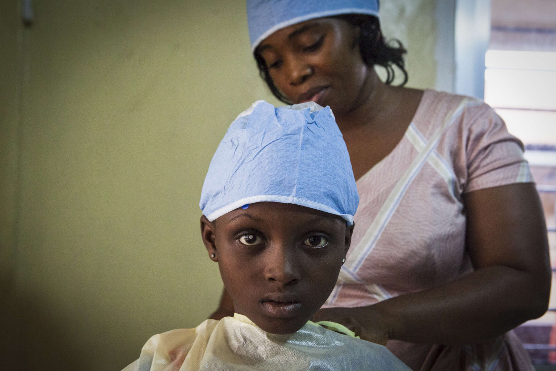Aminata Conteh, 8, puts on a hospital gown before doctors remove fluid from her problematic right eye for testing at the Kissy United Methodist Church Eye Hospital in Freetown, Sierra Leone. Long after recovering from the largest Ebola outbreaks in history, survivors continue to experience debilitating complications including uvetis, an inflammation of the eye, leading to severe cataracts leaving the survivor with little to no sight in the affected eye. Doctors from Emory University Hospital have traveled to Sierra Leone to restore the sight of survivors suffering from severe cataracts in an effort to help them return to a more normal life.