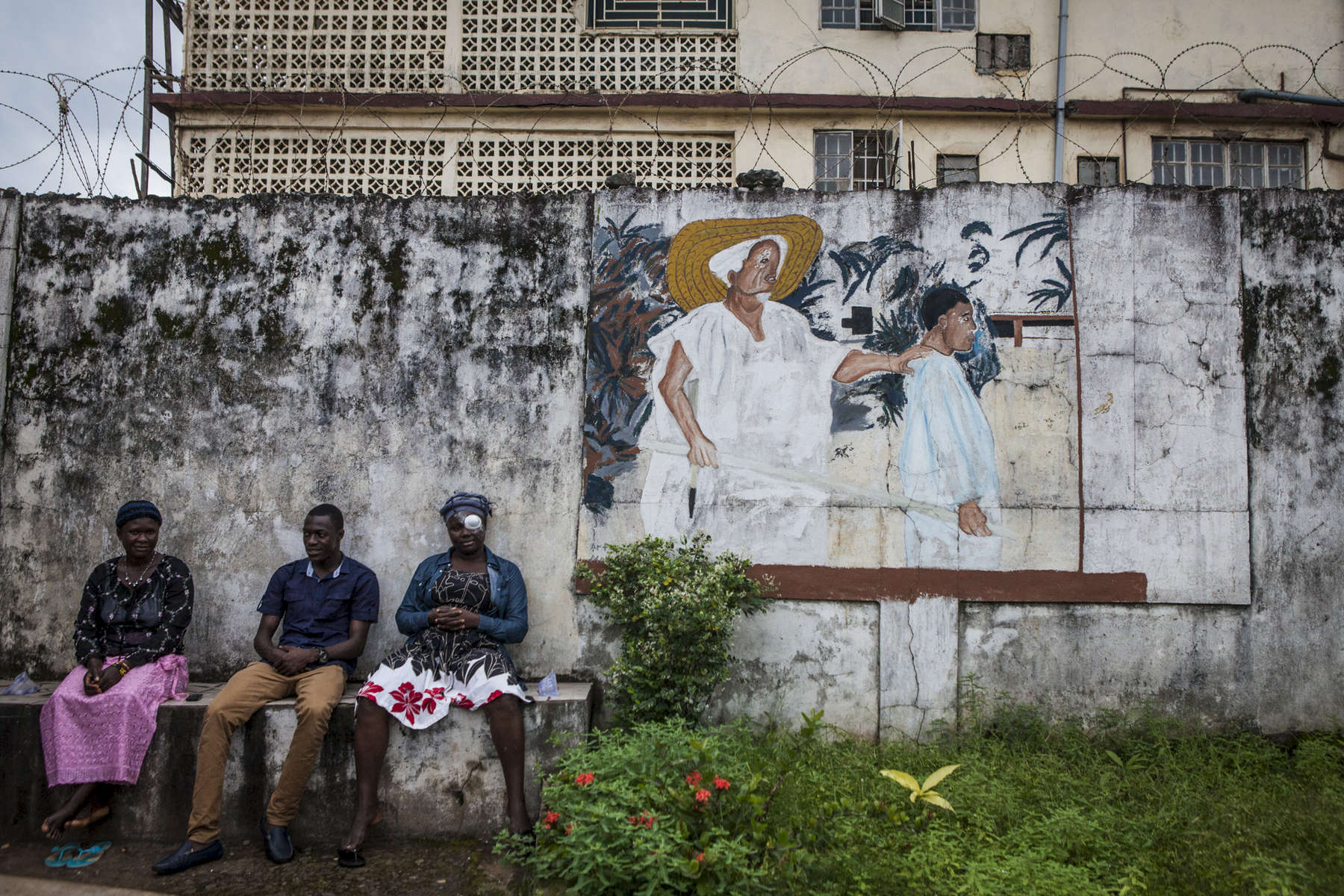 Patients sit on a bench at the entrance of the Kissy United Methodist Church Eye Hospital in Freetown, Sierra Leone
