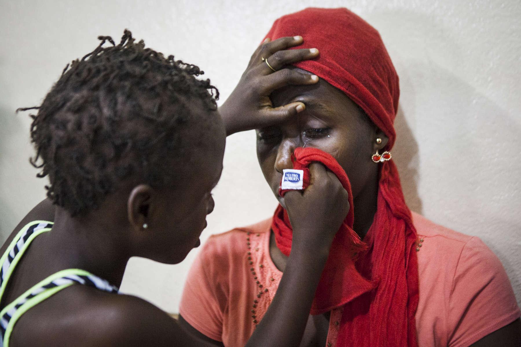 Aminata Conteh, 8, carefully wipes around the eye of a fellow ebola survivor at the Kissy United Methodist Church Eye Hospital in Freetown, Sierra Leone.
