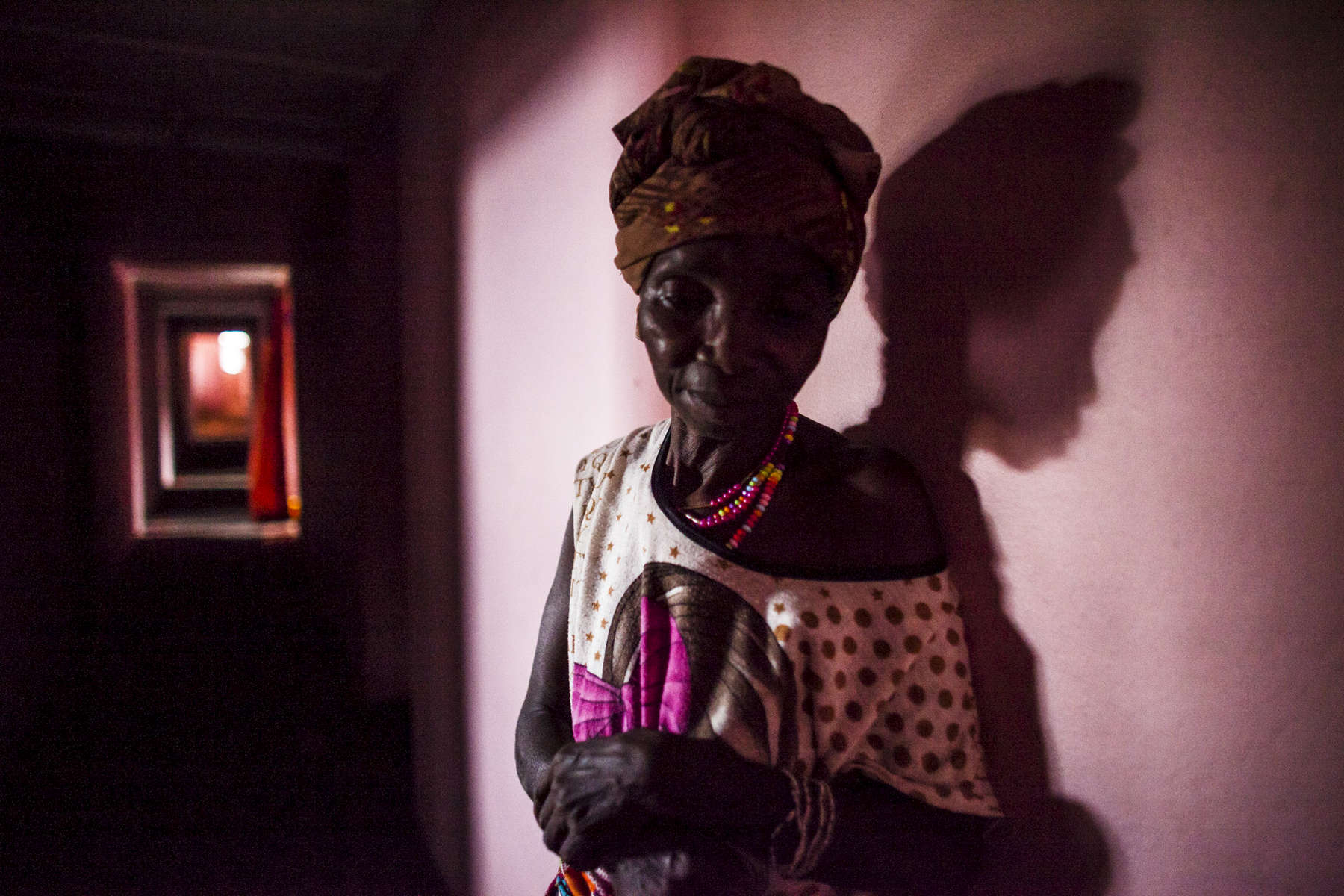 Koloneh Koroma, 6os, left with cataracts in both her eyes after recovering from the Ebola virus stands in the hallway of her guesthouse in Freetown, Sierra Leone.