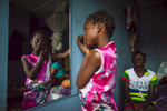 Ebola survivors Aminata Conteh, 8, looks in the mirror as Isatu Tholley, 12 looks on at their guesthouse in Freetown, Sierra Leone.