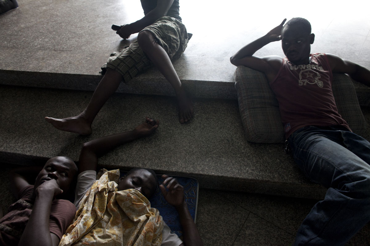 Young men rest on the floor of the St. Paul's Cathedral where over 1600 displaced people have been residing for the last two weeks in Abidjan, Ivory Coast in April 2011. After months of post election violence and thousands of deaths, Laurent Gbagbo finally ceded power to Alassane Ouattara with the backing of French and UN forces allied with the FRCI.