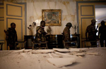 Republican Forces soldiers walk through the damaged presidential dining room at the Presidential Palace in Abidjan, Ivory Coast in April 2011. Days after Laurent Gbagbo ceded power after heavy attacks by the French and Republican Forces, control has been established of the palace after looting took place.  .(Jane Hahn)