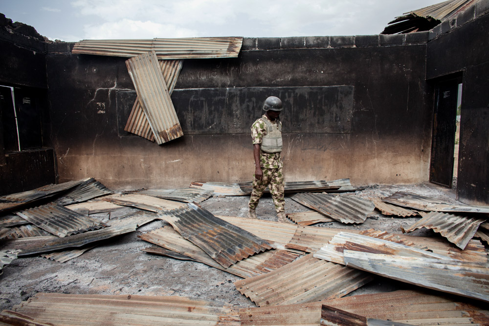 A member of Nigeria's military walks through a destroyed school in Gwoza, Nigeria in April 2014.