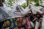 Displaced women and children take cover under a tarp from the rain in Maiduguri, Nigeria.