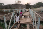 Children cross a dilapidated bridge outside the Moroccan UN Peacekeeper base between the Castors neighborhood and PK5 in Bangui, Central African Republic.