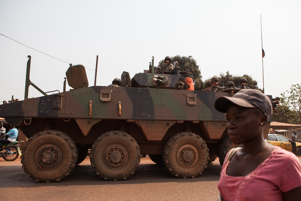 A French military amoured vehicle passes a woman on the streets of Bangui, Central African Republic