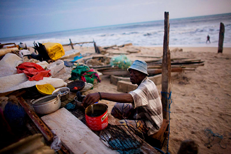 Months later, Kposo sorts through the remains of his belongings after his home is destroyed by three nights of extremely high tides in Totope, Ghana.