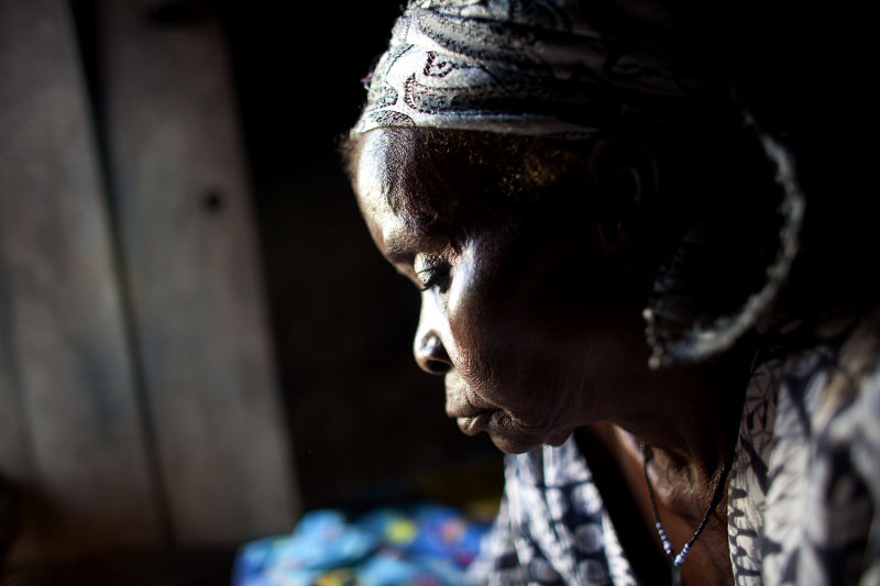 Alleged witch Issahaku Awaba, 70s, looks through old photos of her family in Kukuo Village, Northern Ghana