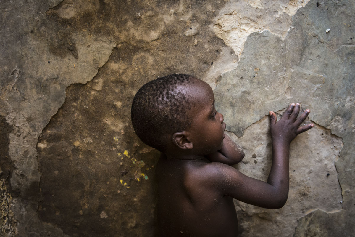 A young boy plays with cracks in the concrete at an internment camp for ex-Boko Haram combatants in Goudoumaria, Niger on Thursday, August 2018.